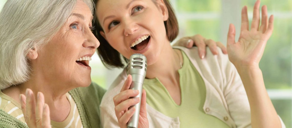 Senior woman with daughter singing on microphone
